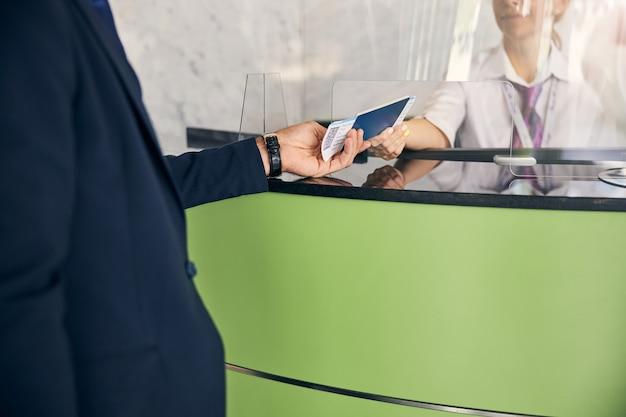 Photo recadrée d'un membre du personnel de l'aéroport rendant les documents de voyage au passager