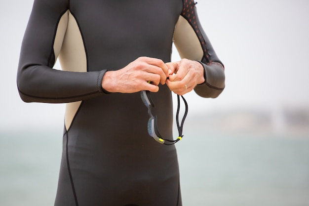 Photo recadrée d'un nageur tenant des lunettes