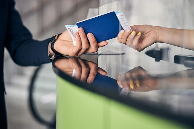 Photo recadrée d'un passeport et de billets d'avion transmis des mains des passagers à un membre de l'équipage de l'aéroport