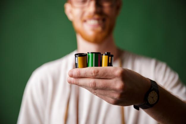 Photo recadrée d'un photographe barbu à tête de lecture, tenant des rouleaux de caméra,