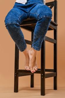 Photo recadrée de pieds nus d'une femme assise sur une chaise