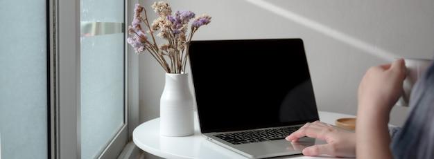 Photo recadrée de pigiste travaillant sur ordinateur portable avec vase à fleurs à la maison
