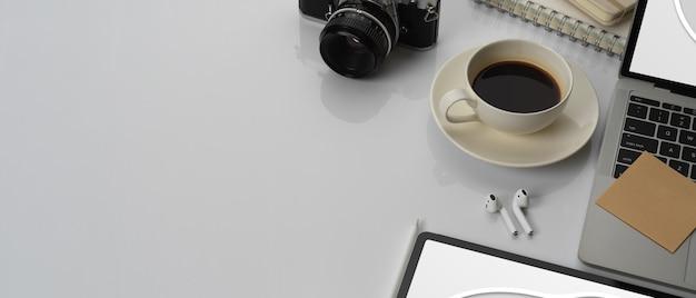 Photo recadrée d'une table de travail avec espace copie, ordinateur portable, maquette de tablette, tasse à café et accessoires