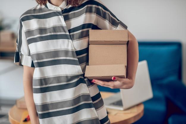 Photo recadrée d'une travailleuse de race blanche avec une pile de boîtes en carton debout à l'intérieur