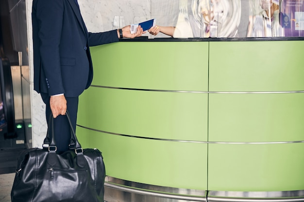 Photo recadrée d'un voyageur donnant ses documents de voyage pour un contrôle de sécurité au bureau de l'aéroport