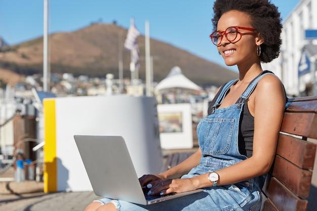 Photo d'un rédacteur ou d'un pigiste satisfait des informations sur les claviers sur le clavier d'un ordinateur portable, pense à quelque chose de créatif, porte des vêtements décontractés, mannequins sur un banc en plein air, travaille en freelance, utilise la 4g
