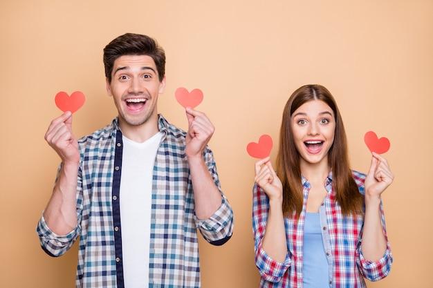 Photo de redhair rouge joyeux décontracté élégant joli charmant beau couple se réjouissant d'avoir reçu de nouvelles petites cartes postales rouges isolées sur fond pastel de couleur beige