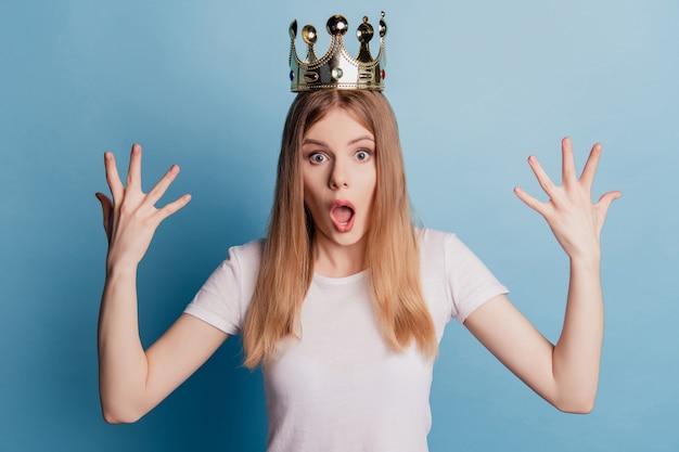Photo d'une reine excitée portant une couronne dorée lever les paumes omg réaction inattendue aux nouvelles sur fond de couleur bleue