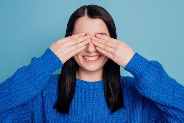 Photo de rêveuse fille ludique paumes fermer les yeux sourire rayonnant heureux incognito isolé fond de couleur bleu