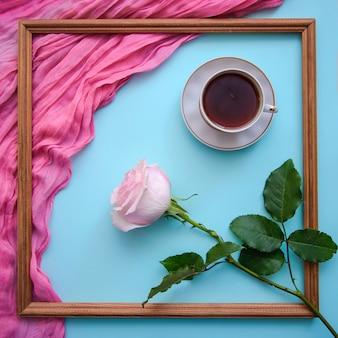Photo romantique avec cadre en bois, thé, bloc-notes et rose