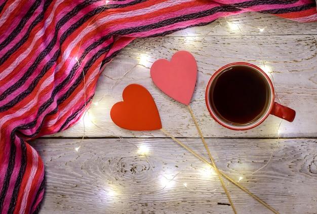 Photo romantique avec une tasse de thé, une écharpe à rayures, deux coeurs rouges et des lumières magiques sur un fond en bois