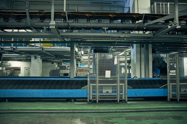 Photo sans personne d'un tapis roulant dans une zone de traitement et de tri des bagages de l'aéroport