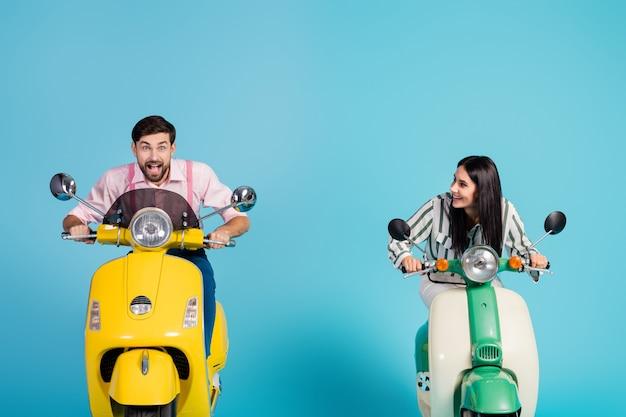 Photo de se précipiter drôle deux personnes dame guy conduire rétro cyclomoteur voyageurs à grande vitesse évitant les embouteillages moyen facile bonne humeur vêtements de cérémonie mur de couleur bleu