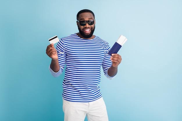 Photo de séduisant voyageur guy peau sombre acheter des billets avec l'aide de la carte de crédit visa porter des lunettes de soleil chemise marin rayé gilet short blanc isolé mur de couleur bleu