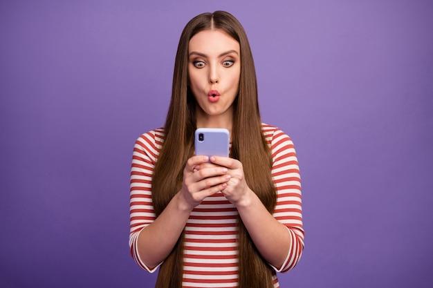 Photo de séduisante dame curieuse choquée regarder l'écran du téléphone bouche ouverte lire les commentaires négatifs nouveau blog post porter chemise rayée décontractée mur de couleur violet pastel