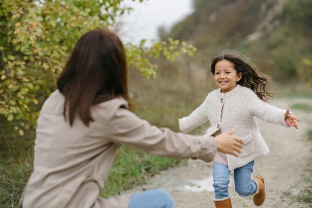 Photo sensuelle. jolie petite fille. les gens marchent dehors. femme en manteau marron.