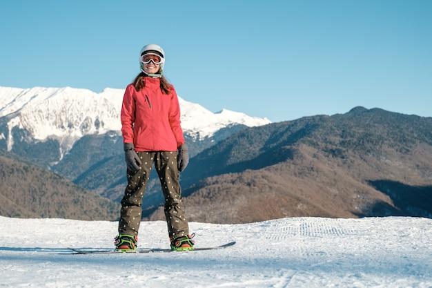 Photo de snowboarder heureux jeune femme sur les pistes