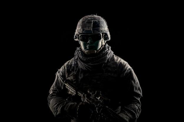 Photo de soldat sur fond noir. soldat des forces spéciales des états-unis ou entrepreneurs militaires privés tenant un fusil. image sur fond noir. concept de soldat, d'armée, de guerre, d'arme et de technologie.
