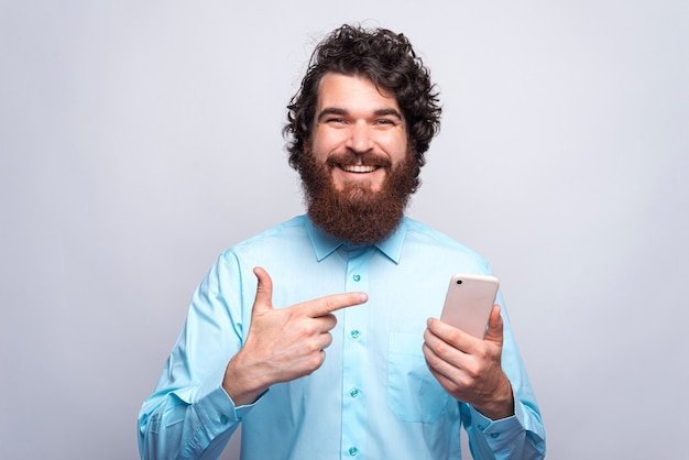 Photo de souriant jeune homme hipster barbu pointant sur smartphone sur mur blanc