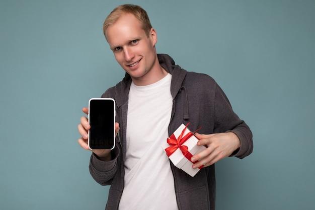 Photo de sourire cool beau jeune homme heureux portant un pull gris et un t-shirt blanc debout