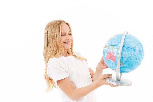 Photo de sourire jeune fille blonde dans des vêtements décontractés tenant globe sur blanc