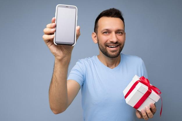 Photo de sourire positif beau jeune homme brunet mal rasé avec barbe portant un t-shirt bleu de tous les jours