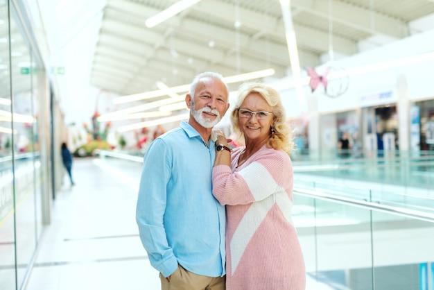 Photo de sourire de vieux couple marié posant dans le centre commercial.