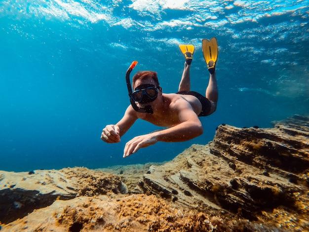 Photo sous-marine d'hommes plongeant en apnée dans l'eau de mer