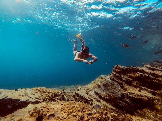 Photo sous-marine d'hommes plongeurs plongeant en apnée dans l'eau de mer