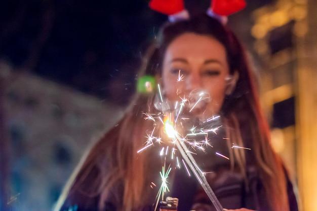 Photo de sparkler avec une femme en arrière-plan. bonne année. gros plan, femme, tenue, sparkler, rue