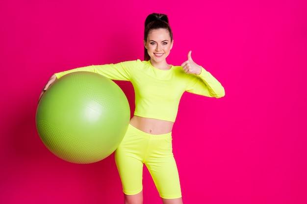 Photo d'une sportive positive tenir le symbole du pouce vers le haut du fitball show isolé sur fond de couleur rose vif