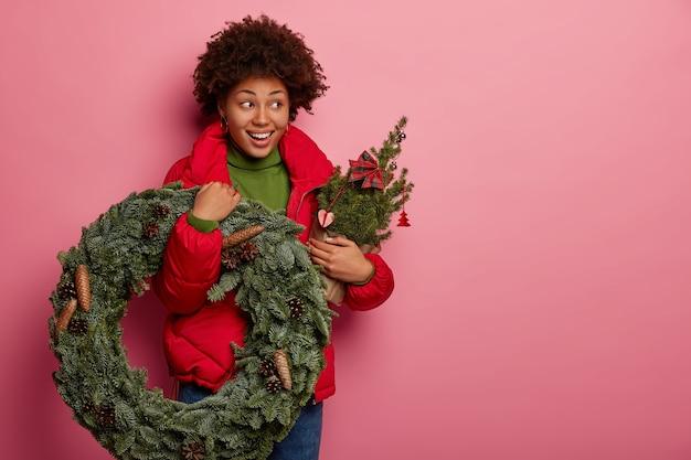 Photo de studio de beau modèle à la peau sombre porte une couronne de noël et sapin décoré, a une ambiance festive, porte des vêtements d'extérieur rouge, isolé sur fond rose