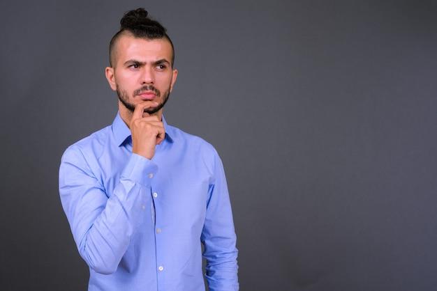 Photo de studio de bel homme d'affaires turc sur fond gris