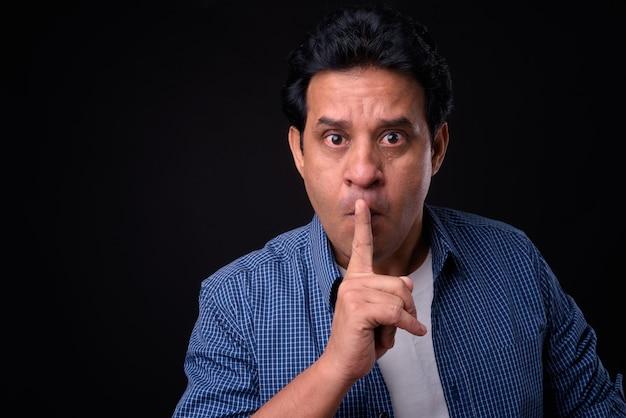 Photo de studio de bel homme indien mature sur fond noir