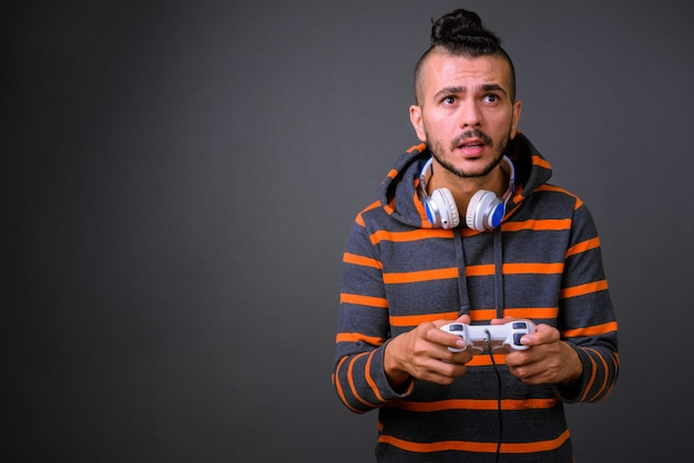 Photo de studio de bel homme turc jouant à des jeux sur fond gris