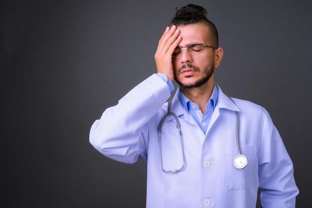Photo de studio de bel homme turc médecin sur fond gris