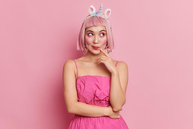 Photo de studio de belle femme réfléchie aux cheveux roses regarde de côté