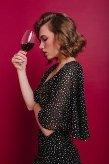 Photo de studio de belle femme sérieuse posant avec un verre de vin