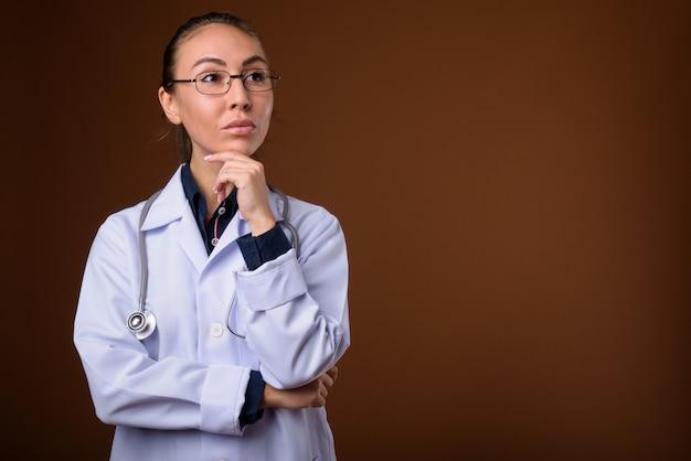 Photo de studio de belle jeune femme médecin sur fond marron