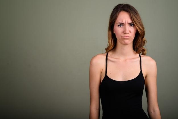 Photo de studio de belle jeune femme portant haut sans manches sur fond coloré