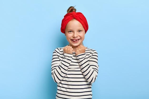 Photo de studio de belle petite fille élégante avec bandeau rouge posant