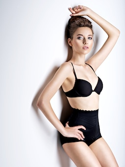 Photo de studio de belle et sexy fille aux cheveux bruns portant de la lingerie noire