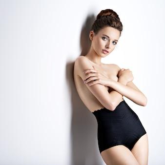 Photo de studio de belle et sexy jeune femme vêtue de lingerie noire