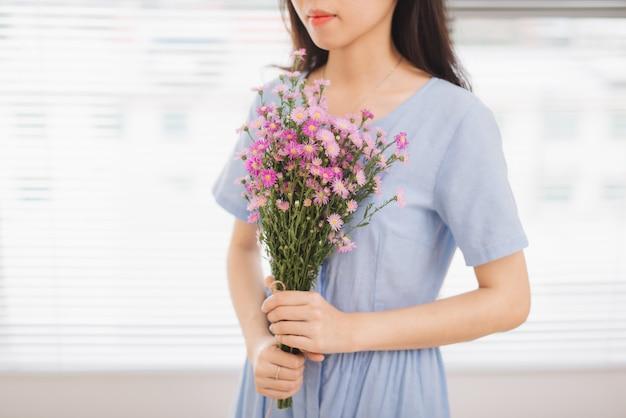 Photo de studio de bonheur femme recevant de jolies fleurs
