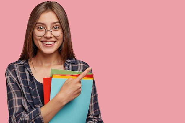 Photo de studio de bonne jeune femme d'affaires posant contre le mur rose avec des lunettes