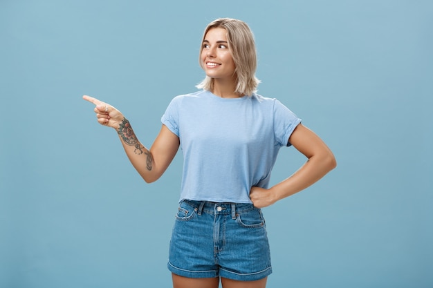 Photo de studio de charmante jeune femme européenne intriguée avec une peau bronzée et des cheveux blonds tenant la main sur la taille dans une pose confiante pointant vers la gauche avec intérêt et curiosité