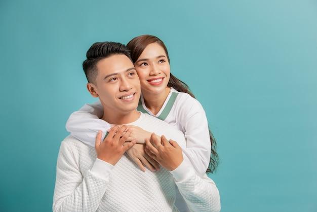 Photo de studio de couple romantique posant avec le sourire. vue de face des câlins fille et garçon sur bleu.