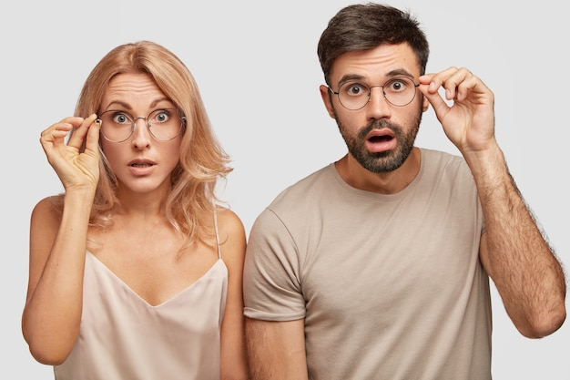 Photo de studio de deux femme et homme formidables surpris regardent perplexe, toucher le bord de lunettes, étonné par des nouvelles soudaines
