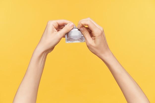 Photo de studio de deux mains levées soulevées lors de l'ouverture du pack avec préservatif, va avoir des relations sexuelles protégées, isolé posant sur fond orange. concept de mains humaines