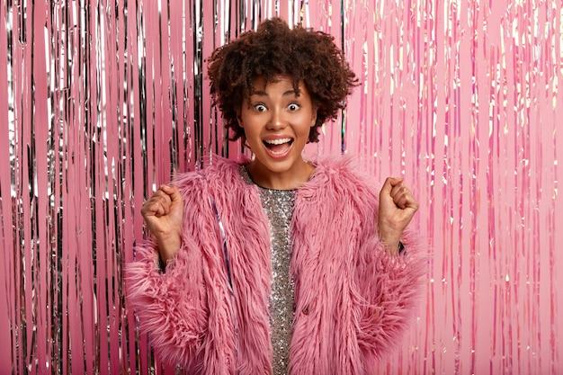 Photo de studio d'une femme afro-américaine optimiste serre les poings, a une réaction heureuse en entendant sa chanson préférée à la fête